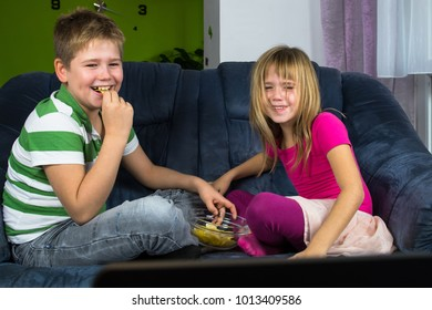 Children are looking at the televison together at the living room and eating chips.