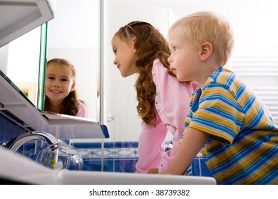 children looking at their reflection in the mirror