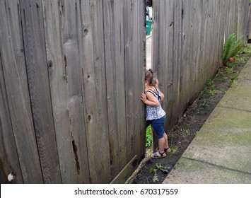 children are looking through the hole in the fence