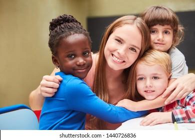 Children lovingly embrace their kindergarten teacher in the kindergarten or daycare