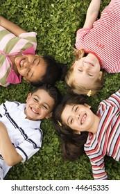 Kinder, die zusammen in Klee liegen mit Köpfen. Vertikal gerahmte Aufnahme.