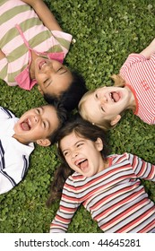 Children lying in clover screaming and laughing with heads together. Vertically framed shot.