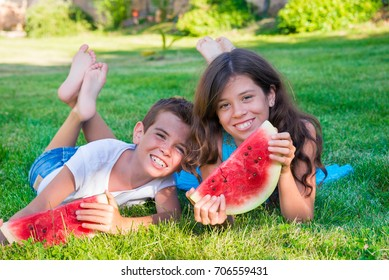 Children lying on grass and eating watermelon