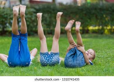 Children lying on green grass in park on a summer day with their