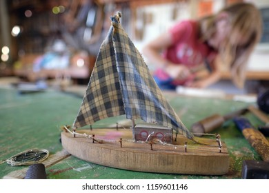 Children make wooden sailing boats in a club workshop