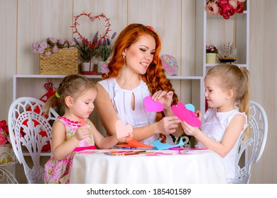 Children making cards  together with a nursery teacher