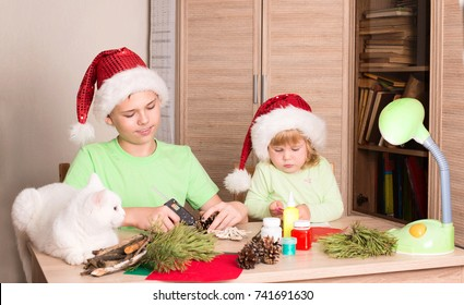 Children making Christmas decorations with cat on the table. Make christmas decoration with your own hands. Handcraft concept.