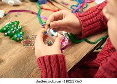 Children making decorations for new year holiday. Painting with watercolors. Top view. Artwork workplace with creative accessories.
