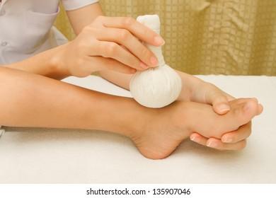 Children massage foot with herbal compress balls