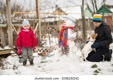 Children mold Snowman with a carrot in the yard winter, Boy and girl play with snow