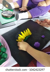 Children are molding banana plasticine clay on black flute board.
