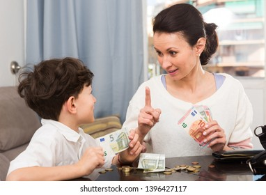 Children and money concept. Woman admonishing teen boy while giving him money at home