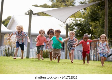 Children At Montessori School Having Fun Outdoors During Break