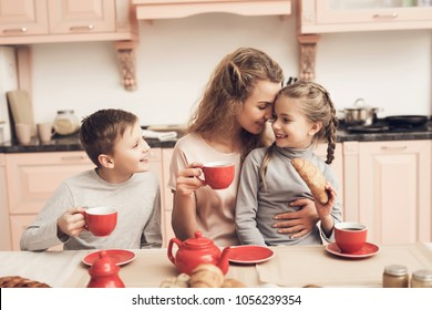 Children with mother at kitchen table in kitchen. Family is drinking tea with croissants.