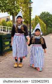 Children in national vintage Dutch costumes. Two girls are dressed in vintage Dutch clothes and shod in wooden clogs. Children walk along the street and smile.