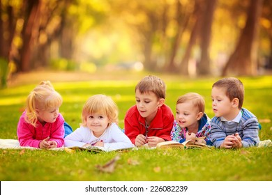 children in nature. reading a book outdoors lying on the grass