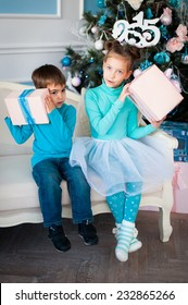 children near a Christmas tree with gifts
