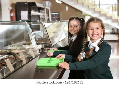 Children near serving line with healthy food in school canteen