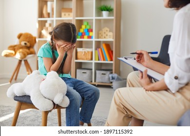 Children need help. Bullied little schoolgirl crying in psychologist's office unable to control emotions, sharing problems and traumas. Professional psychotherapist talking to distressed bully victim