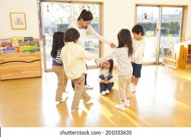 children and a nursery teacher dancing in a circle