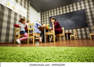 Children and nursery teacher sit at desks in classroom at child club, low angle view, focus on floor covering, shallow dof.