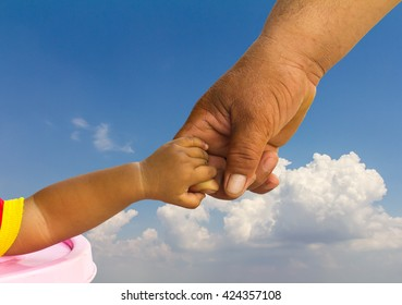 Children are obese, which is a hand to hold his parents cloudy sky as a backdrop.