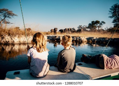 Children observing elephants at the riverside of Kwando River at Sunset, Caprivi, Namibia