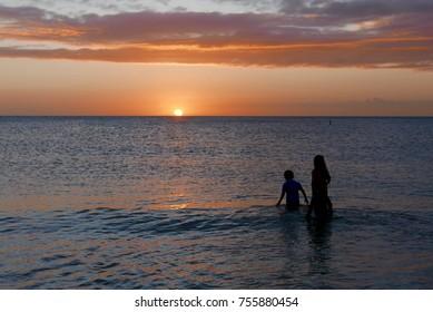 Children in the ocean watching the sun set