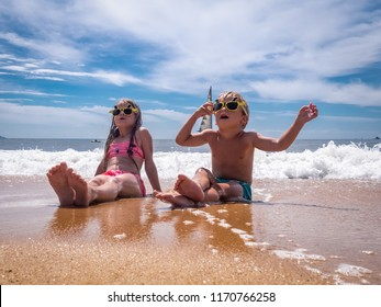 Children on the beach: A boy and a girl in funny sunglasses are sitting on the seashore in sea foam. In the background a sailboat sails.