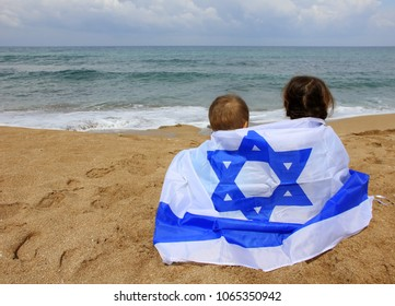 children on the beach with the flag of Israel