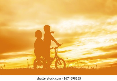 Children on bicicles in a sunset
