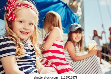 The children on board of sea yacht drinking orange juice. The teen or child girls against blue sky outdoor. Colorful clothes. Kids fashion, sunny summer, river and holidays concepts.