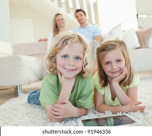 Children on the carpet together with tablet and parents behind them