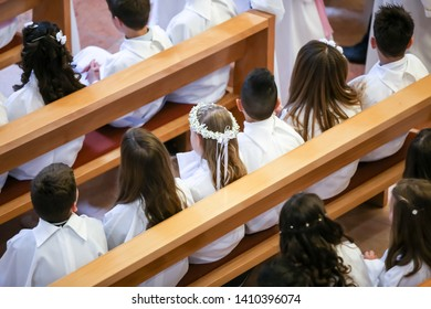 Children on the first holy communion in the church. View from above of children sitting in the bench during the first holy communion mass.