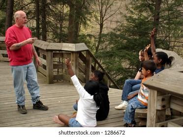 Children on a nature walk, focus on the teacher.