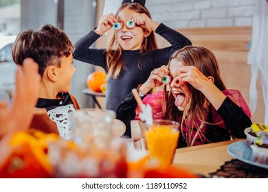 Children on party. Three beaming children with bright painted faces wearing costumes having Halloween party