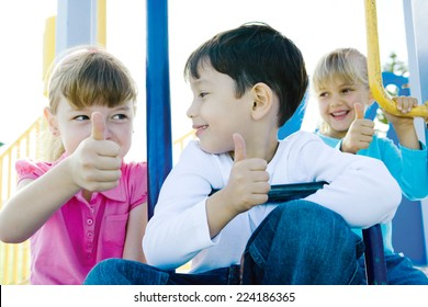 Children on playground equipment, giving thumbs up sign