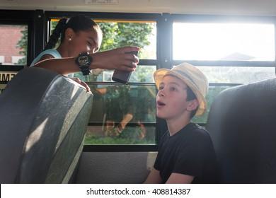 Children on the School bus - Girl showing friend her smart phone