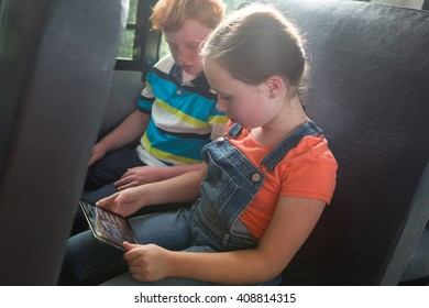 Children on the School bus looking at tablet computer