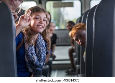 Children on the School bus - smiling girl with classmates