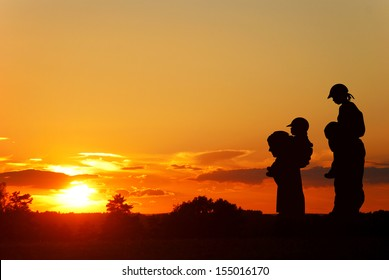 children on the shoulders of parents go summer evening, silhouettes on sunset