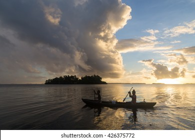Children on the way to school with a canoe during sunrise in the Solomon Islands.