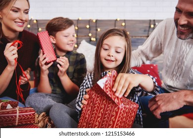 Children opening christmas present with parents