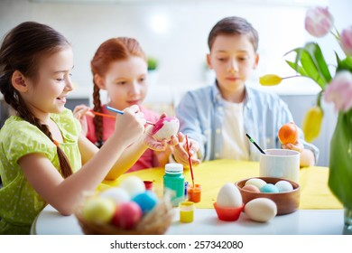 Children painting eggs at school