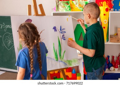 Children painting on easel. Girl with boy learn paint in class school. Child picture on background. Drawing on the easel.
