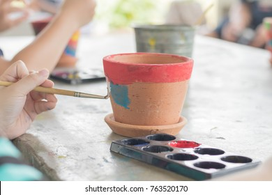 Children are painting potted plants made of pottery.