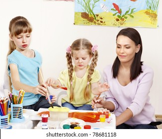 Children painting in preschool. Teacher help by little girl.