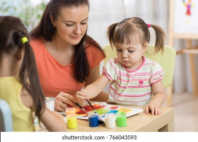 Children painting in preschool. Teacher helps by kid little girl.