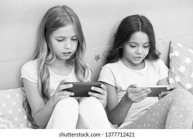 Children in pajama interact with smartphones. Application for kids fun. Internet surfing and absence parental advisory. Smartphone internet access. Girls sisters wear pajama busy with smartphones.