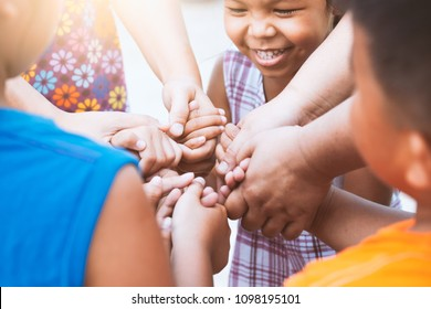 Children and parent holding hands and playing together with unity and teamwork